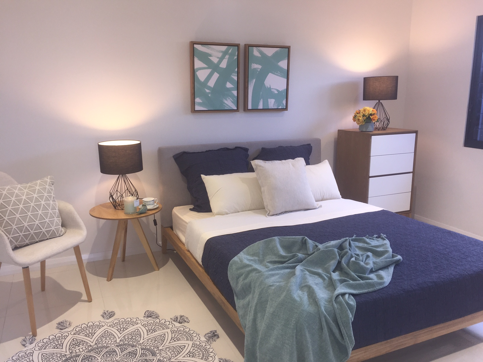 modern bedroom with lamps, blue bed and side chair